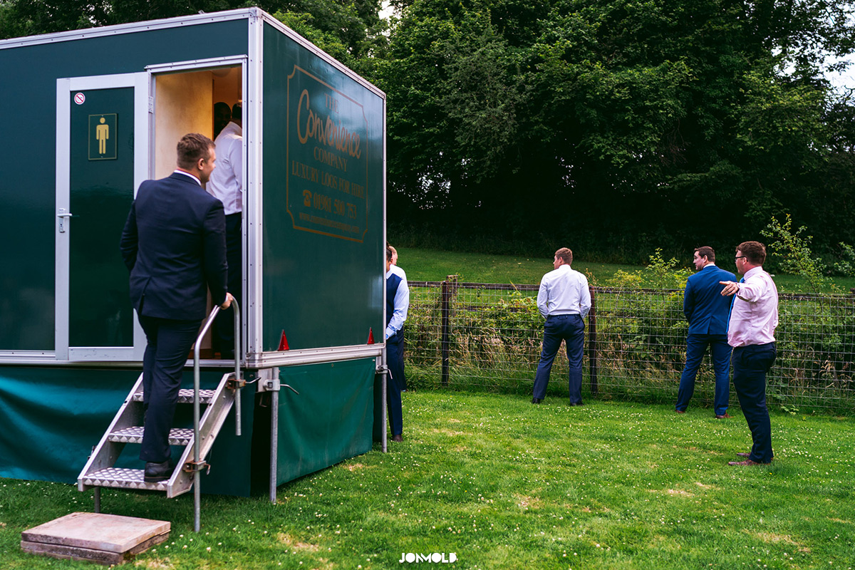 men peeing outside mobile toilets at wedding